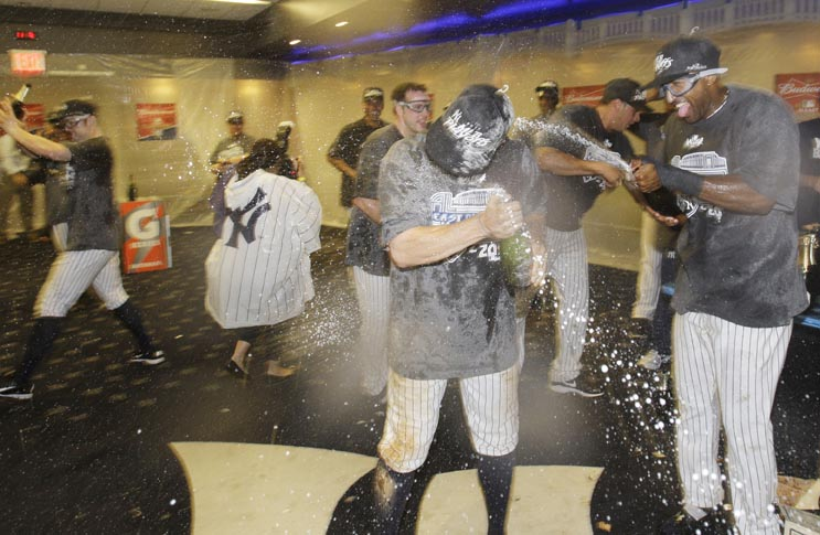 The Yankees celebrate after clinching the AL East title with a 4-2 win over the Tampa Bay Rays in the second game of a baseball doubleheader Wednesday.