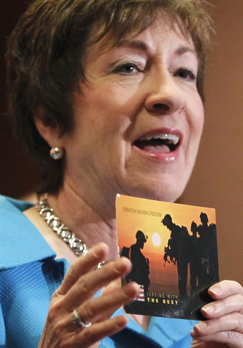 Sen. Susan Collins, R-Maine, holds up a postcard she received from an anonymous Army soldier in Afghanistan thanking her for her support of the repeal of