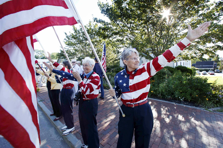 In this Aug. 23, 2011, photo, the Freeport Flag Ladies wave to cars in Freeport. The women, who have waved the American flag every Tuesday morning since 9/11, have dedicated their lives to encouraging the American spirit and supporting of U.S. troops in the war against terrorism.