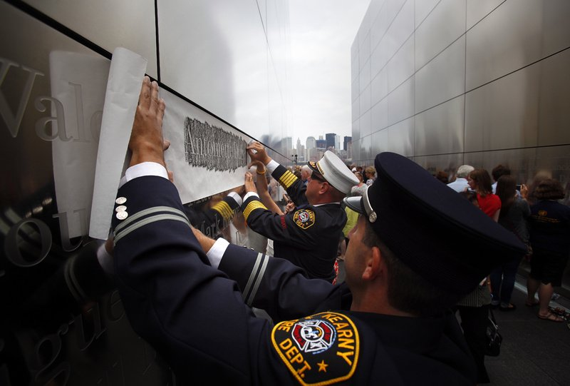 Kearny, N.J., Fire Chief Steve Dyl etches the name of a 9/11 victim for a friend with the help of Capt. Joseph Mastandrea at the Empty Sky memorial dedication Saturday at Liberty State Park in Jersey City, N.J. The memorial, situated on the Hudson River, is in remembrance of the 746 people from New Jersey who died in the Sept. 11, 2001, attacks. It was designed to aim directly at ground zero in New York to offer a connector between the two states. The memorial's two 30-foot-high towers stretch 208 feet, 10 inches long, the width of the original World Trade Center towers.