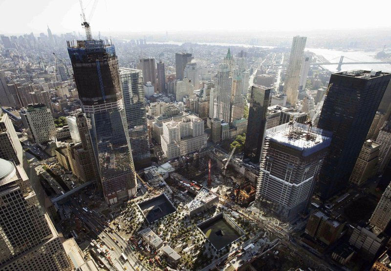 Construction continues at the World Trade Center in New York. One World Trade Center, left, rises above the lower Manhattan skyline followed by Four World Trade Center, lower right, with the square outlines of the almost-completed September 11 Memorial at lower center.