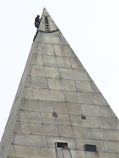 A man attaches rigging to the top of the Washington Monument on the National Mall today, before engineers rappeled down the sides of the monument to survey the extent of damage from the Aug. 23 earthquake.