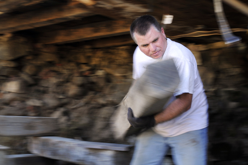 Gabe Souza/Staff Photographer: Ken Watson of Saco works to remove a support from underneath the Burnham House on Route 111 in Arundel, on Monday, September 12, 2011. The house, built in 1795, is one of two houses being raised from its foundation and moved by the Arundel Historical Society.