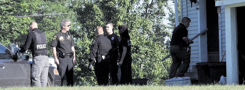 Winslow Police Chief Jeffrey Fenlason, second from left, speaks with other officers at a residence at 632 Benton Ave. in Winslow on Aug. 23.
