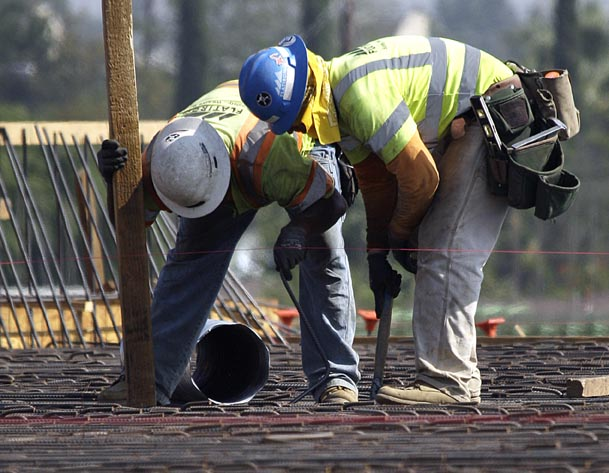 Construction workers check rebar on a highway construction project on Interstate 5 in Los Angeles Wednesday. The number of people seeking unemployment benefits fell sharply last week, an encouraging sign that layoffs are easing. The Associated Press
