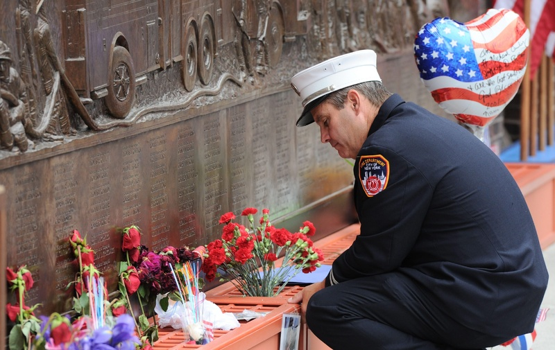 A New York city firefighter pauses at the firefighters memorial wall that displays the names of victims of Sept. 11 at ground zero on the 10th anniversary of the terrorist attacks in New York today. Canada Canadian 9/11 9-11 nine eleven Sept 11 Sept. 11. Terror Terrorism plot NY NYC