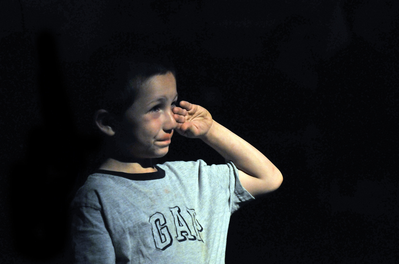 Staff photo by Michael G. Seamans Jasper Ruiz, 6, of North Anson, wipes a tear from his cheeck during the singing of the National Anthem at the beginning of the September 11th memorial sercvice at Champions on Main Street in Waterville Saturday.