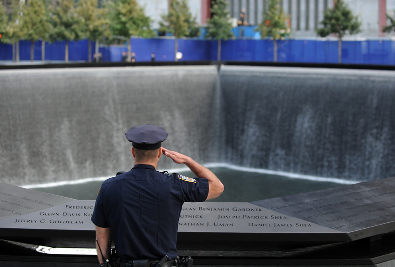 A New York City police officer salutes at the north pool of the Sept. 11 memorial as the national anthem is sung during the 10th anniversary ceremonies at the World Trade Center today in New York.