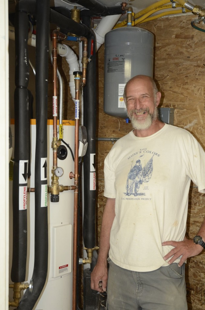 Paul Ledman proudly displays his house's hot water system.