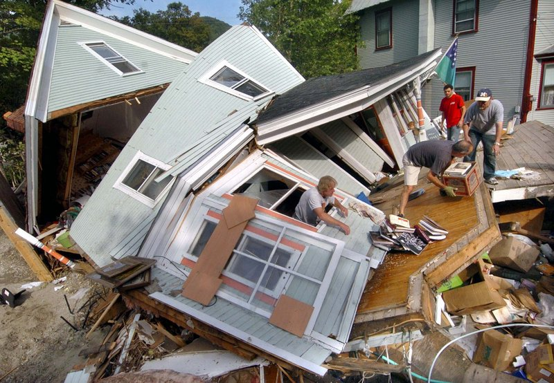 Homeowner Jon Graham, right, gets help removing items from his destroyed home in Rochester, Vt., on Wednesday. The house collapsed into the Brook Street Brook during Tropical Storm Irene.