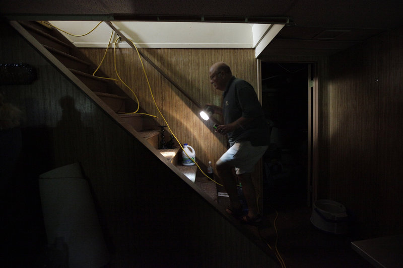 Without power since Tropical Storm Irene hit the state Sunday, Ron Corsi heads up the stairs from the basement of his house in Havertown, Pa.