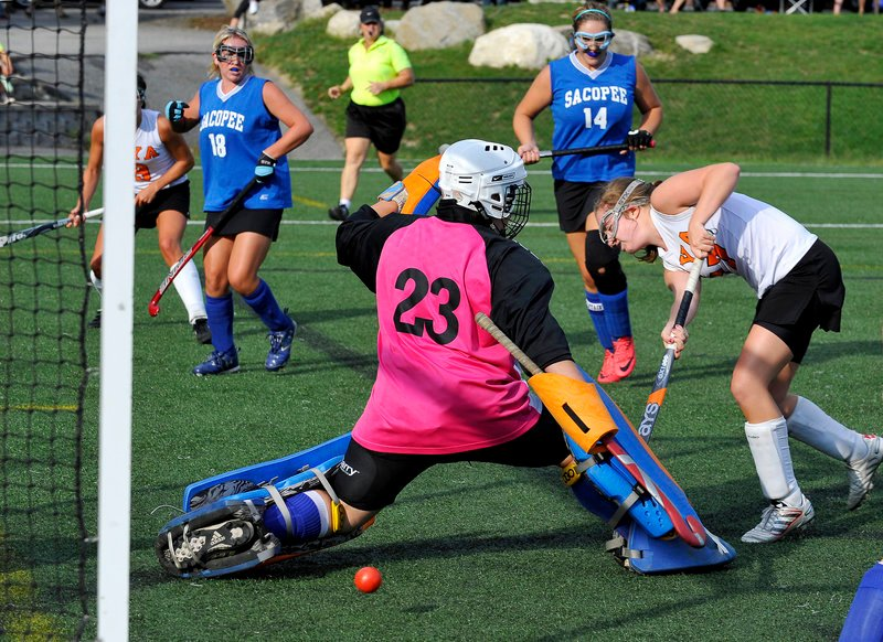 Katie Cawley of North Yarmouth Academy tucks a shot under Sacopee Valley goalie Ashley Pingree during their field hockey opener Thursday. Katherine Millett, left, provided the assist. Defending for Sacopee were Rachel Anderson (18) and Christina Metcalf. NYA won, 4-1.