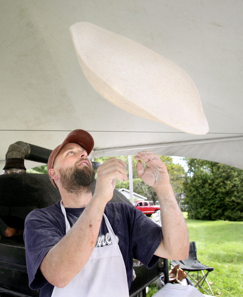 Bennett Collins, owner of Harvest Moon Pizza, hand-tosses his dough and tops his pies with organic ingredients. On this day, he had his mobile wood-fired oven stationed along Route 1B in Damariscotta.