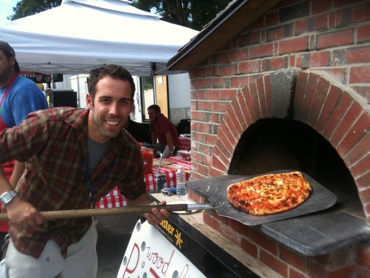 Ryan Carey of Pizza Pie on the Fly removes one of his creations from his oven at the recent KahBang festival in Bangor.
