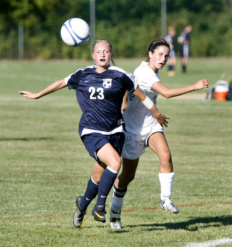 Kayla Swasey, left, of York tries to keep Waynflete's Katherine Harwood from the ball while on the run Friday in a girls' soccer game at Portland. Swasey had a goal and an assist in the Wildcats' season-opening 8-0 victory.
