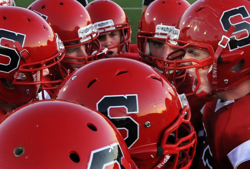 Scarborough team captain Logan Mars, right, pumps up his teammates before the Red Storm's high school football season opener against Class A rival Windham on Friday night. Scarborough won the game, 21-6.