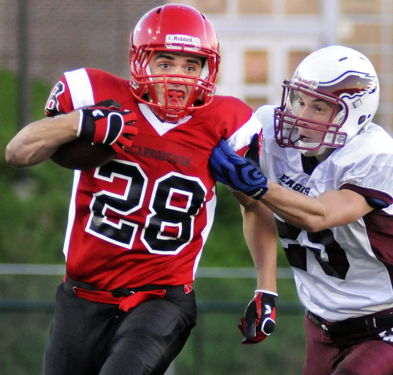 Scott Thibeault of Scarborough breaks away from Jordin Allen of Windham for a long gain in the first quarter Friday night. Thibeault finished with 274 yards on 28 carries and scored two touchdowns as the Red Storm opened with a 21-6 victory at home.