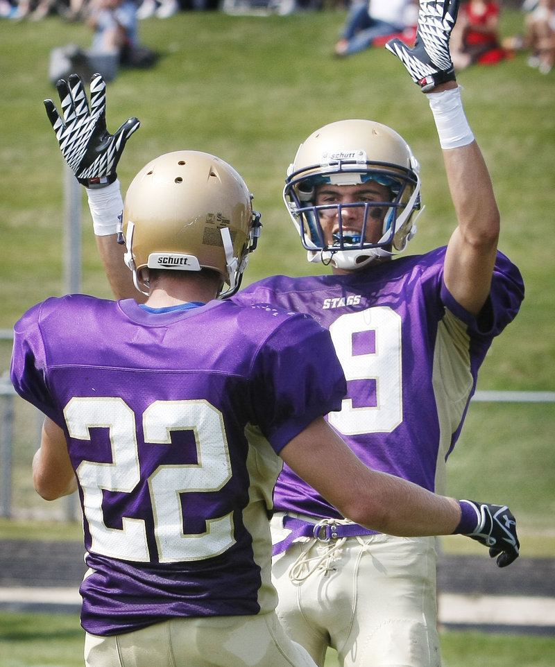 Louie DiStasio of Cheverus raises his hands to congratulate teammate Donald Goodrich after Goodrich scored a second-quarter touchdown Saturday during the season-opening 59-21 victory against South Portland.