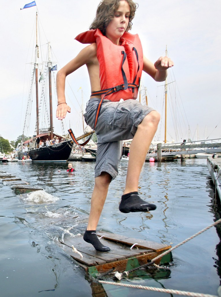 Aidan Acosta, 13, of Rockport leaps for the dock while competing in the lobster crate race on Saturday during the Camden Windjammer Festival.