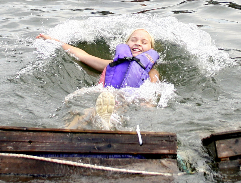 Abby Doherty, 10, of Kennebunk keeps smiling after taking a plunge during the lobster crate race.