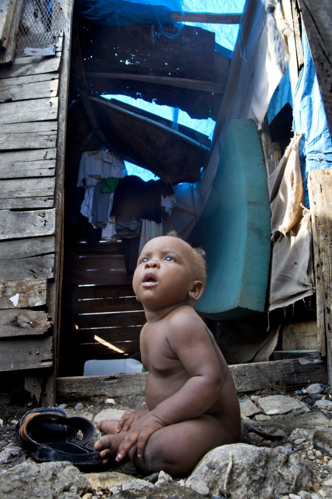 A baby boy sits outside his family's makeshift home last month in the Champs de Mars tent city near the crumbling National Palace in Port-au-Prince, Haiti.