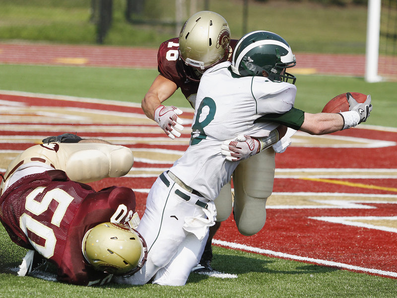Andrew Libby of Thornton Academy puts a high hit on Matt Burnell of Bonny Eagle, forcing a fumble that ended the Scots' final opportunity. Making the lower-body hit for the Golden Trojans is Chris Madden.