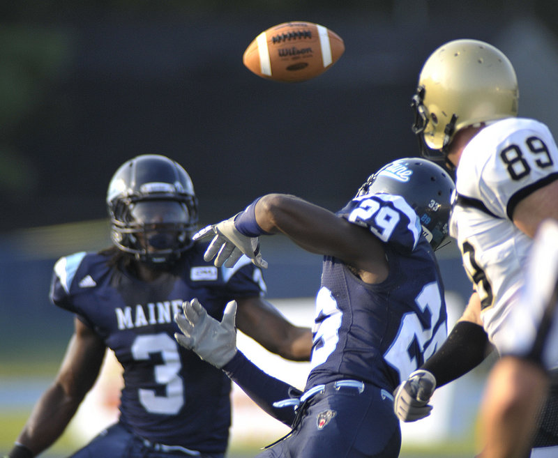 Darlos James (29) tries to knock down a pass intended for Bryant University's Matthew Hunt, right, in the first quarter of Maine's 28-13 victory Saturday at Orono.