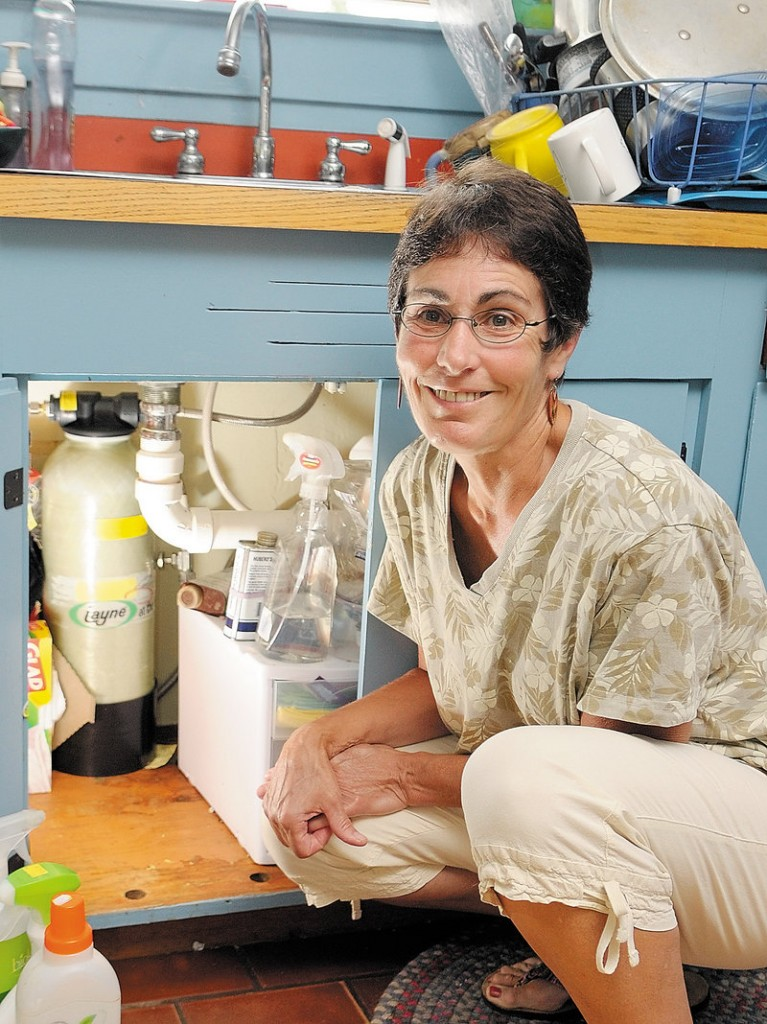 Beth Nagusky uses an under-the-sink filtration system to remove arsenic from the well water at her home in Litchfield.