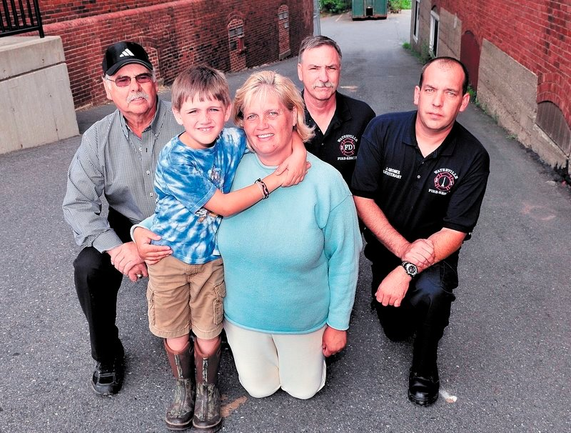 Robert Maxwell Freedom Clark and his mother, Terri Clark, pose Wednesday with Waterville firefighters Capt. Roland LaCroix, left, Robert Shay and John Gromek, who helped deliver the boy nine years ago Sunday in an alley next to the original Central Fire Station. The birth occurred on Sept. 11, 2002, a year to the minute after the World Trade Center terrorist attack.