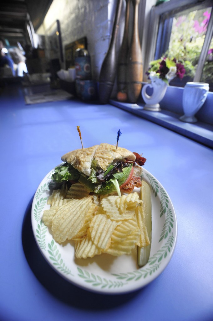 A recent luncheon special: an avocado BLT on homemade three-cheese focaccia, served with chips and a pickle.