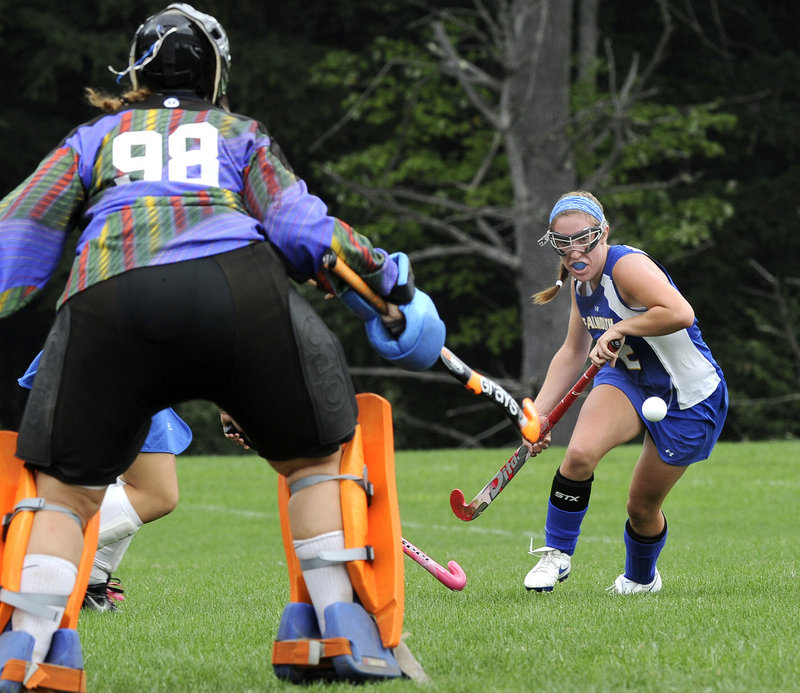 Lake Region goalie Shannon VanLoan moves into position as Falmouth midfielder Megan Fortier looks to control a bouncing ball Monday afternoon during their Western Maine Conference field hockey game in Naples. The teams ended the game tied, 1-1.