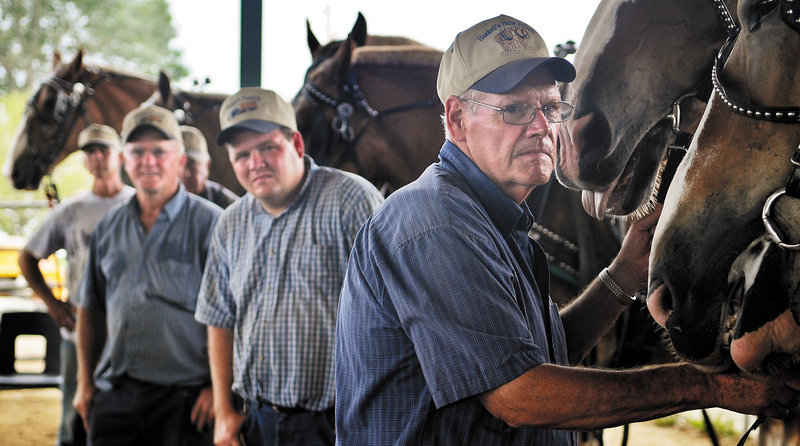Men wait with their teams of horses Monday while watching a pulling competition on the last day of Windsor Fair.