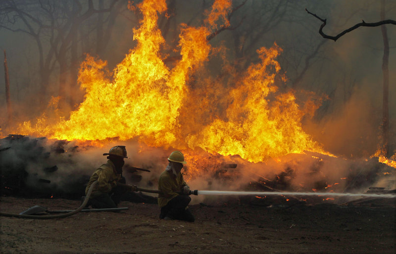 Firefighters battle a large wildfire near Smithville, Texas, on Monday. The blaze has destroyed nearly 500 homes, displaced at least 5,000 people and scorched 25,000 acres.