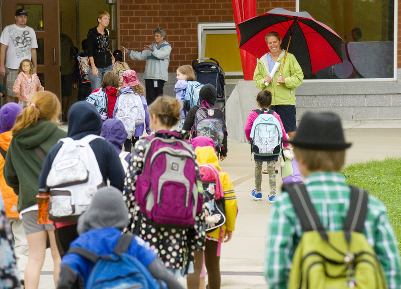 Holding an umbrella, ed tech Jill Marshall has a smile ready Tuesday for incoming Ocean Avenue Elementary students.