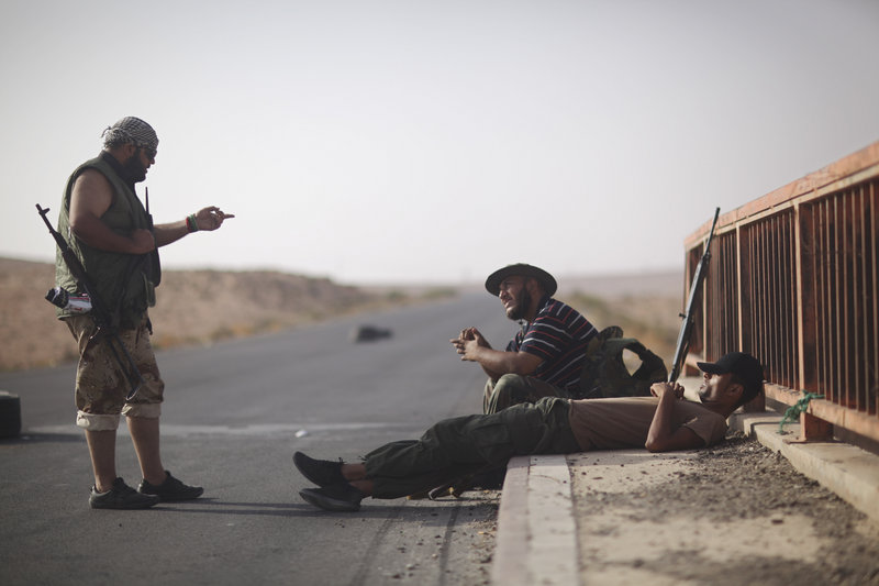 Libyan rebels chat at a checkpoint between Tarhouna and Bani Walid on Tuesday. Moammar Gadhafi is not in the convoys crossing the Sahara, the U.S. State Department said.