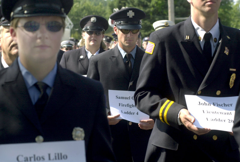 Maine firefighters hold placards with the names of New York firefighters killed on 9/11 as they parade in Freeport to open the Maine State Federation of Firefighters convention in 2002.