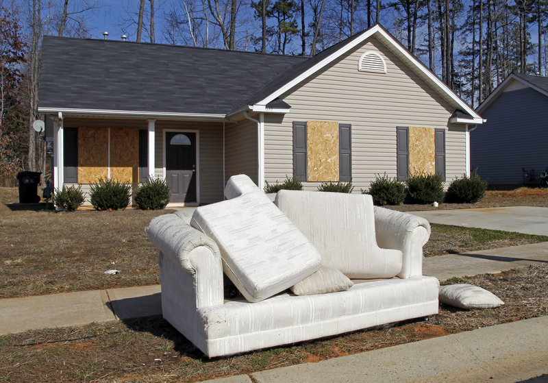 A discarded sofa sits in front of an abandoned house in the Windy Ridge subdivision of Charlotte, N.C., where many sought starter homes in recent years. A Pew Charitable Trusts study has found nearly a third of Americans with a middle-class upbringing have slipped down the economic ladder.