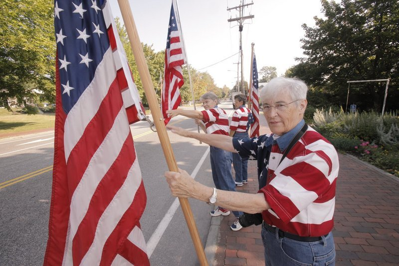The Freeport Flag Ladies, front to back, JoAnn Miller, Elaine Greene and Carmen Footer, wave to passing motorists on Main Street in Freeport in August 2010.
