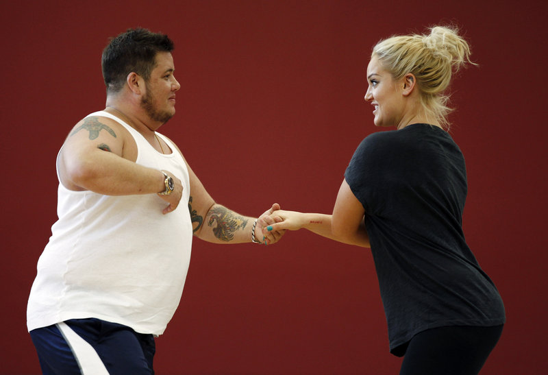 """Chaz Bono, left, and Lacey Schwimmer practice dance steps while rehearsing for the upcoming season of """"Dancing With the Stars,"""" which premieres Sept. 19. Bono is the first transgender contestant, leading some to call for a boycott of the ABC hit."""