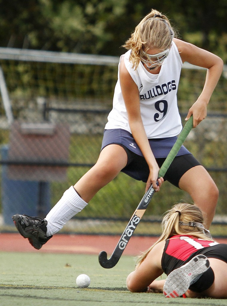 Cat Flaherty of Portland attempts to slap the ball past Olivia Indorf of South Portland, who was defending an empty net Thursday during Portland's 4-1 win in field hockey.