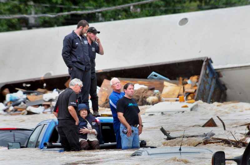 Six people stranded on the back of a pickup truck await rescue as floodwaters rise around them Wednesday in Mount Joy, Pa. Parts of New York also were inundated.
