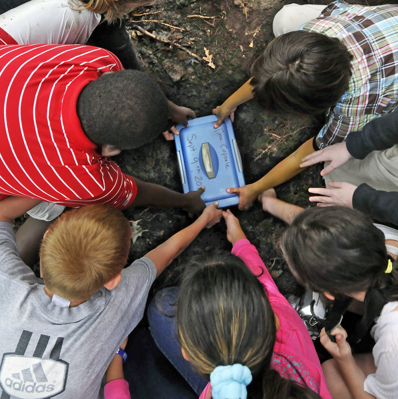 King Middle School students bury their own time capsule in Baxter Woods to replace one left there in 1981 by sixth graders. The badly deteriorated capsule dug up Friday held a slang dictionary, an HBO guide and an Atari catalog.