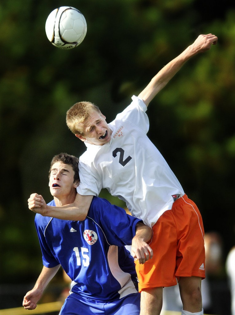 Christopher Bruno of Brunswick goes over Joey Van Note of Mt. Ararat to knock the ball away Friday during their schoolboy soccer game. Each team remained undefeated after a game that ended in a 1-1 tie.