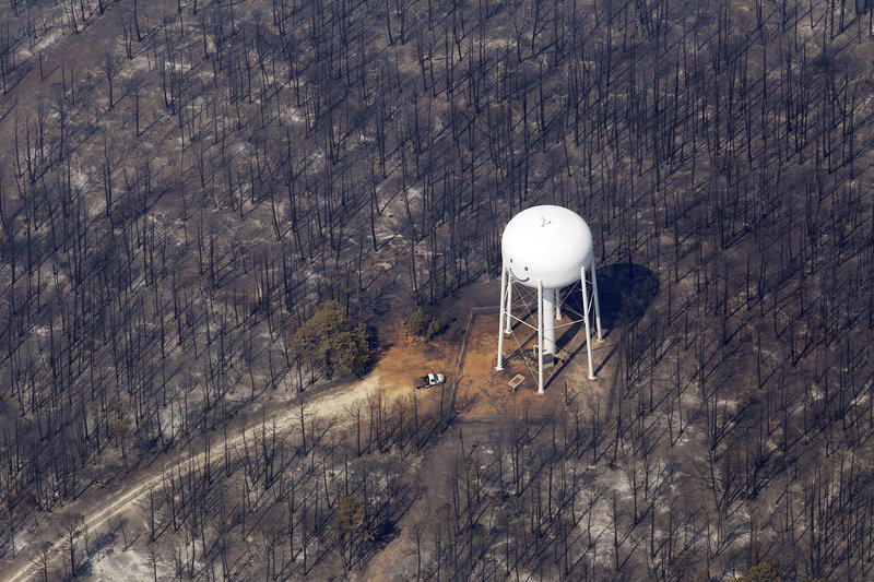 An area destroyed by wildfire surrounds a water tower Wednesday in Bastrop, Texas.