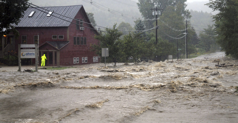 "A rescuer searches a building as floodwaters from Tropical Storm Irene close the main road in Waitsfield, Vt., on Aug. 28. This scene and the one below underscore an ages-old water issue: ""There's enough quantity, but it is not always in the right places,"" said a former federal water regulator."