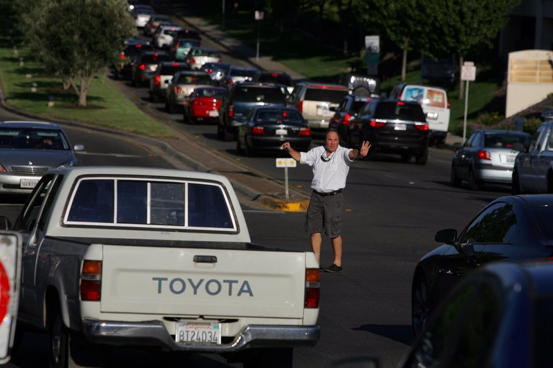 Good Samaritan Dave Eminhizer directs traffic at the intersection of Rancho Bernardo Road and Bernardo Center Drive after a massive power failure Thursday knocked out traffic lights in San Diego.