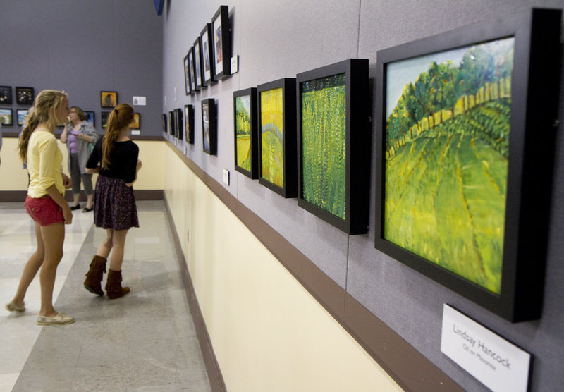 People check out the art at the Black Frame Art Sale in the Merrill Auditorium rehearsal hall Friday. The sale has been going on for eight years, organized by the Bayside Neighborhood Association.