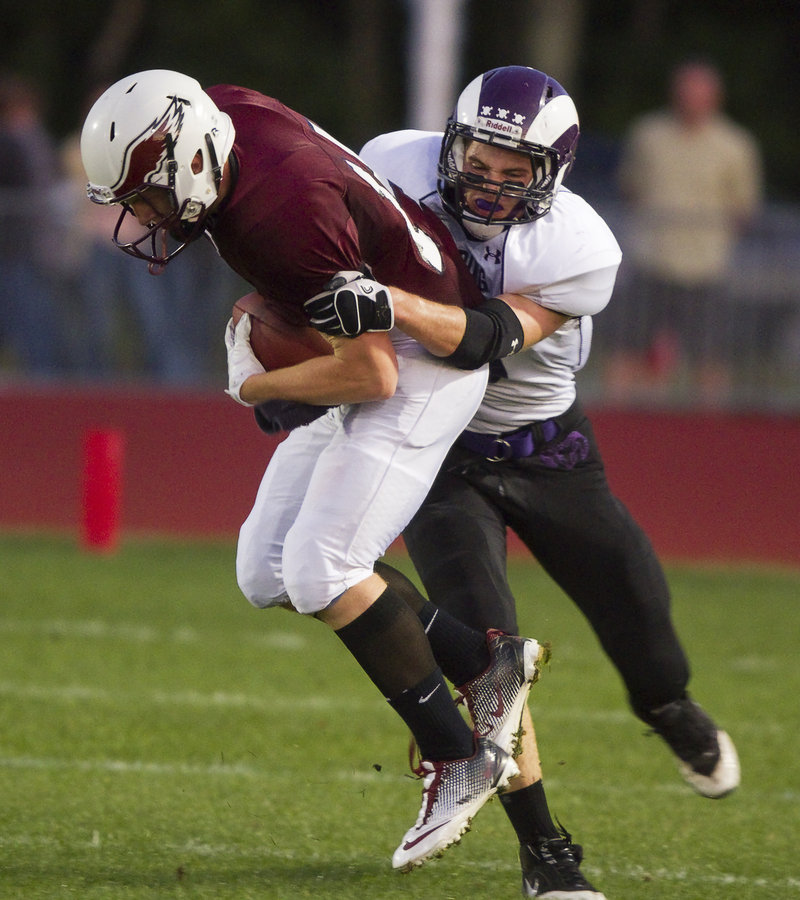 Defensive back Nick DiBiase of Deering isn't letting Windham quarterback T.D. O'Brien go anywhere Friday night during their Western Class A game at Windham High. O'Brien did rush for 157 yards, but Deering improved its record to 2-0 with a 28-20 victory.