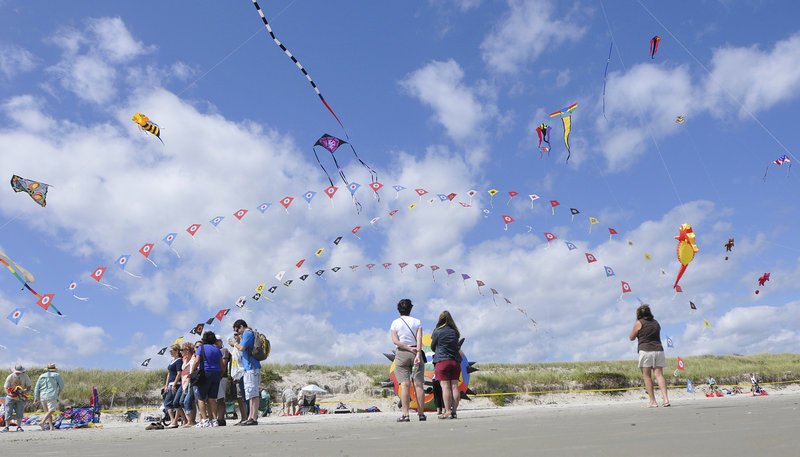 Beachgoers admire the kites in flight on Saturday during the Capriccio Festival of Kites in Ogunquit.