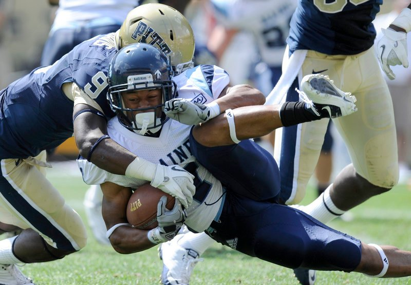 Maine's Roosevelt Boone is tackled by Pittsburgh defensive back Ray Vinopal during the Panthers' 35-29 win Saturday. The Black Bears scored two touchdowns in the final four minutes.